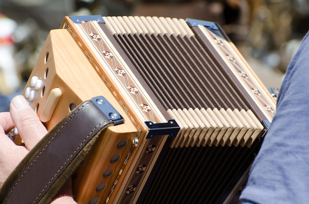 Closeup view of a person holding and playing the accordion