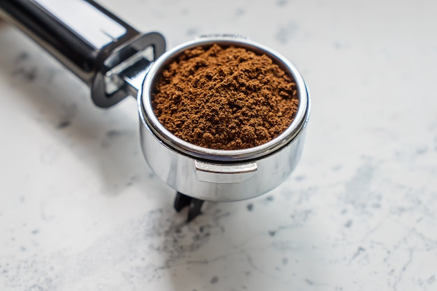 Closeup view of portafilter with ground coffee for coffee machine barista