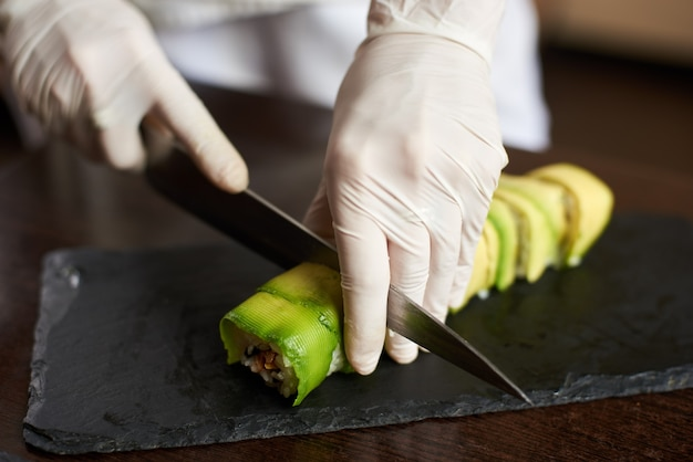 Closeup view of process of preparing rolling sushi. hands in gloves slicing roll on the black stone plate