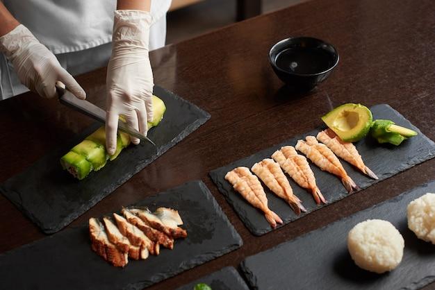 Closeup view of process of preparing rolling sushi