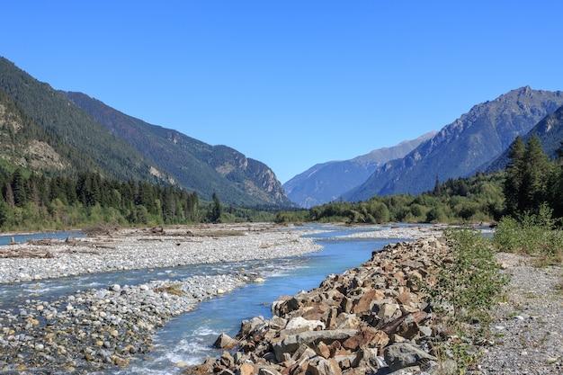 Крупным планом вид речные сцены в горах национального парка домбай, кавказ, россия, европа. летний пейзаж, солнечная погода, драматическое голубое небо и солнечный день