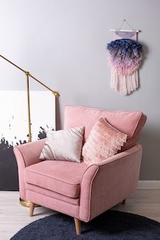 Closeup view of rose nice armchair and gold lamp in light pink stylish apartment side view