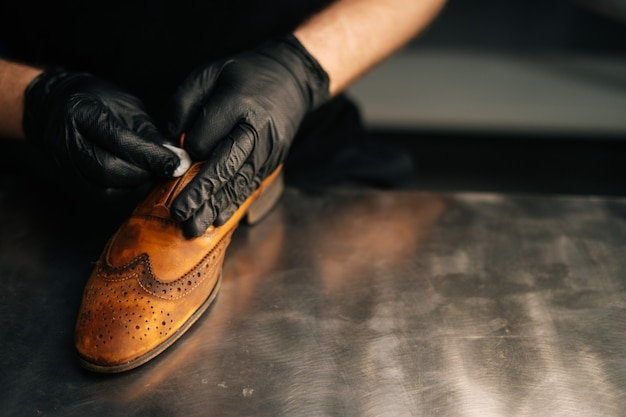 Closeup view of shoemaker wearing black latex gloves cleaning old light brown leather shoes with rag...