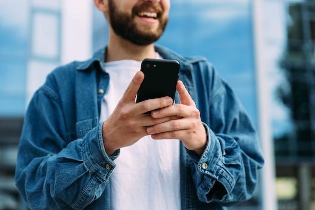 Closeup view of smartphone in hands of smiling bearded male hipster. mobile technology concept.