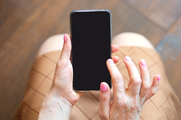 Closeup view of smartphone with black screen in woman hands copy space concept background high