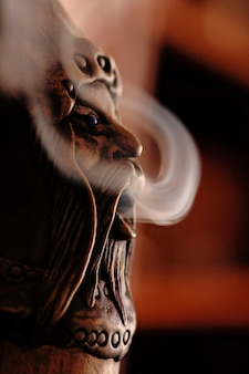 Closeup view of a smoking incense doll with smoke.