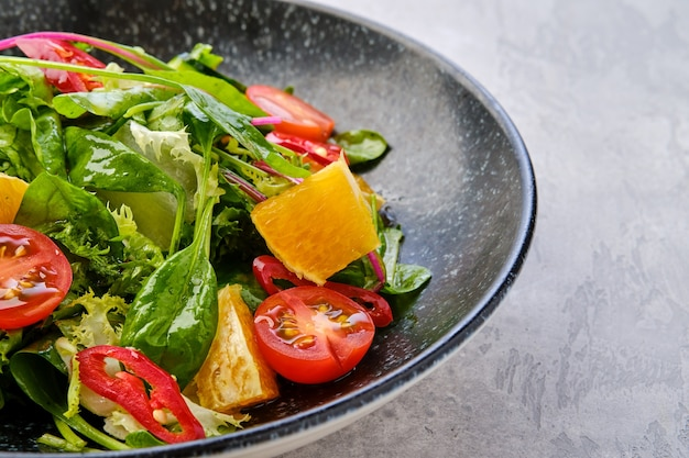Closeup view of spicy salad with orange, chilli pepper, tomato, cucumber and avocado