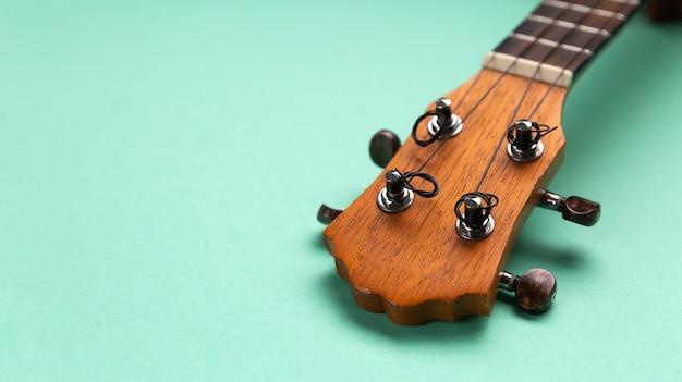 Closeup view of ukulele headstock. cyan background copy space.