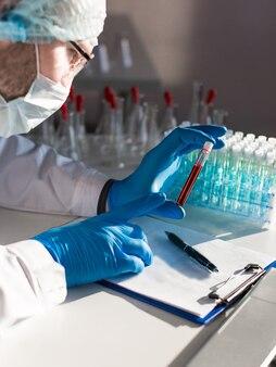 보호 마스크를 쓴 의사의 클로즈업 보기 세로 사진에는 정보 샘플이 들어 있는 테스트 튜브가 있습니다.