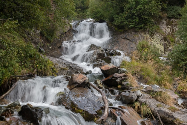 Крупным планом вид водопад сцена в горах, национальный парк домбай, кавказ, россия. летний пейзаж, солнечная погода и солнечный день