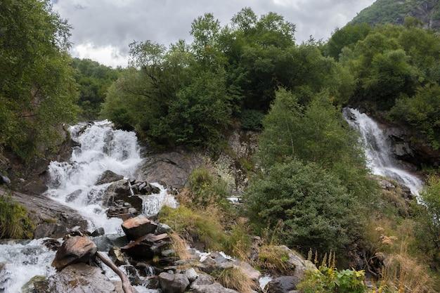 山、ドンベイ、コーカサス、ロシアの国立公園のクローズアップビューの滝のシーン。夏の風景、太陽の光の天気と晴れた日