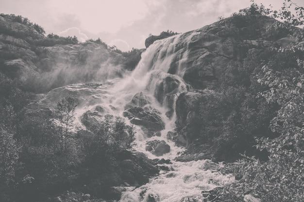 Крупным планом вид водопад сцены в горах, национальный парк домбай, кавказ, россия, европа. летний пейзаж, солнечная погода, драматическое голубое небо и солнечный день