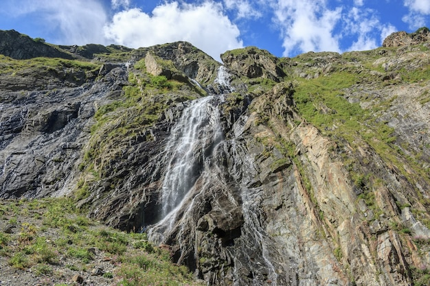 Closeup view waterfall scenes in mountains, national park dombai, caucasus, russia, europe. summer landscape, sunshine weather, dramatic blue sky and sunny day