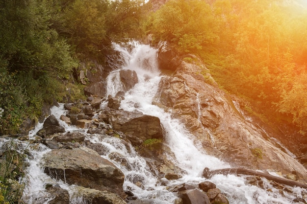 Closeup view waterfall scenes in mountains, national park dombai, caucasus, russia, europe. summer landscape, sunshine weather and sunny day