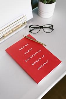 Vista del primo piano di una scrivania bianca con taccuino rosso, penna e occhiali