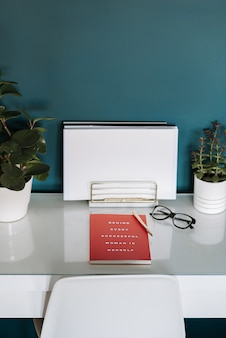Closeup view of a white desk with white papers, red notebook, plants, pen and glasses in it