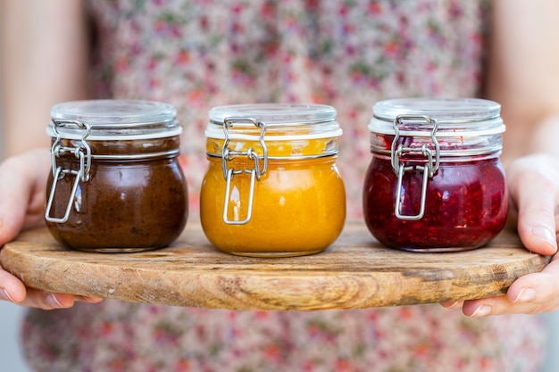 Closeup view of a woman holding a wooden plate with plum, apricot, raspberry jam glass jars