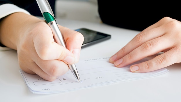 Closeup view of woman writing signature on banking cheque.