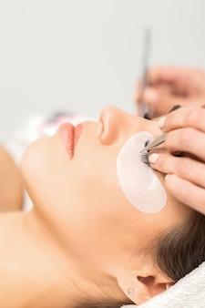 Closeup view of young caucasian woman having eyelash extension procedure in beauty salon. beautician glues eyelashes with tweezers