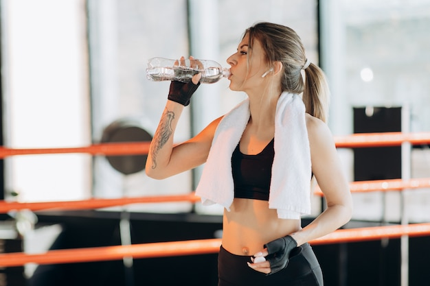 Closeup view of a young woman having a break after hard training by the boxing bag