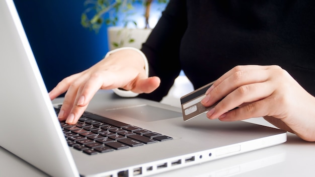 Closeup view of young woman shpping online holding plastic credit card.