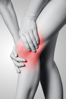 Closeup view of a young woman with knee pain on gray background