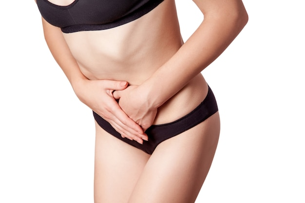 Closeup view of a young woman with stomach pain or digestion or period cycle on white background.