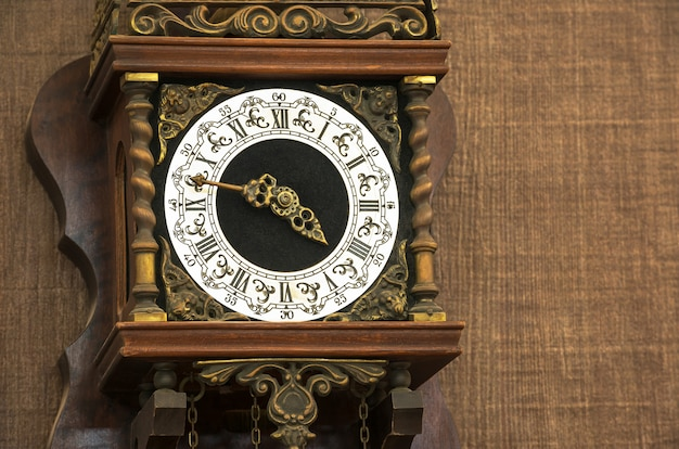Closeup of the vintage clock face hanging on brown wall