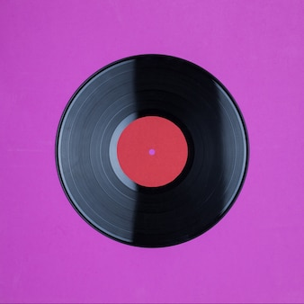 Closeup of vinyl long play record with label with copy space on pink background