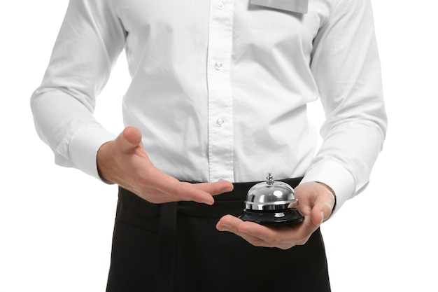 Closeup of waiter holding bell on white surface