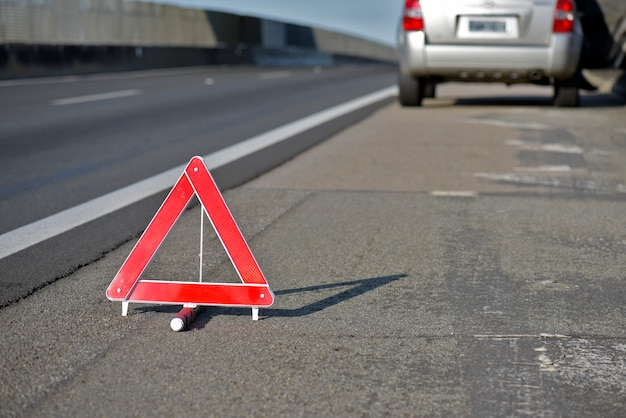 Closeup of warning triangle on roadside with blurred car in background