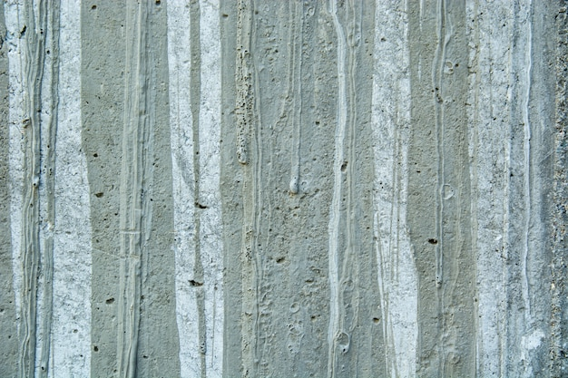 Closeup of a weathered grungy rustic wall with paint spots and old cement