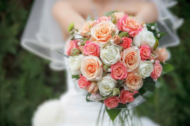 背景に花嫁とクローズアップの結婚式の花束