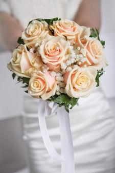 バックラウンドの花嫁とクローズアップのウェディングブーケ