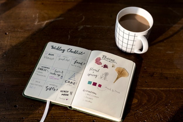Closeup of wedding checklist notebook on wooden tabel Free Photo