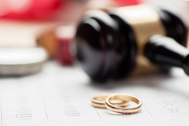 Closeup of wedding rings with gavel hammer on background