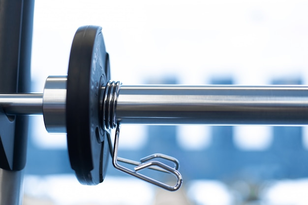 Closeup weight plate fixed on barbell in gym