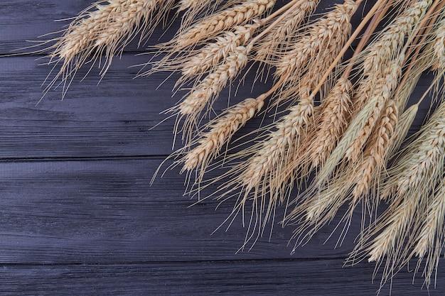 Крупный план зерна пшеницы на черном деревянном фоне