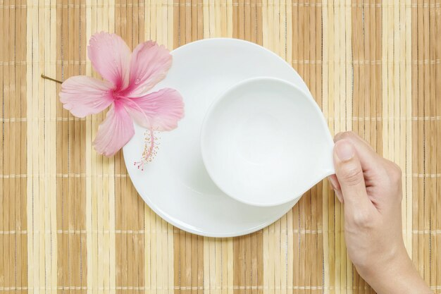 Closeup white ceramic cup for beverage with woman hand on blurred wood mat textured background