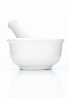 Ступка и пестик крупного плана белые керамические изолированные на белизне.