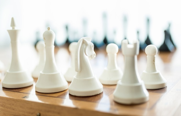 Closeup white chess piece set on wooden board