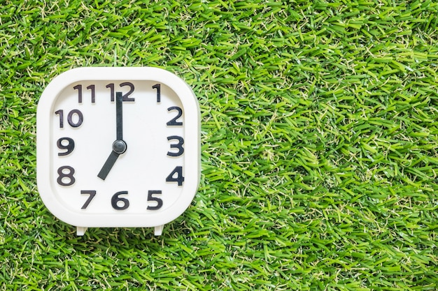 Closeup white clock for decorate in 7 o'clock on green artificial grass floor