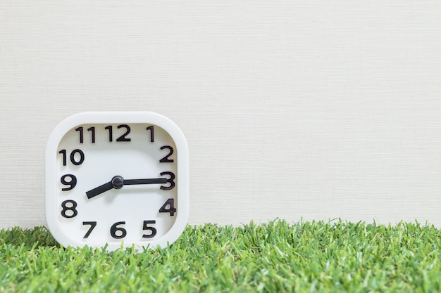 Closeup white clock for decorate show a quarter past eight or 8:15 a.m. on green artificial grass floor