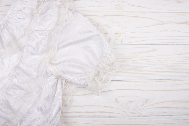Closeup of a white communion or wedding dress on a wooden background