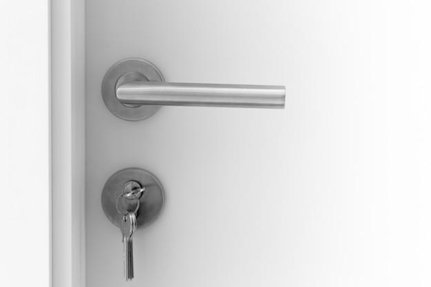 Closeup white door handle metal with key to unlock or locking door