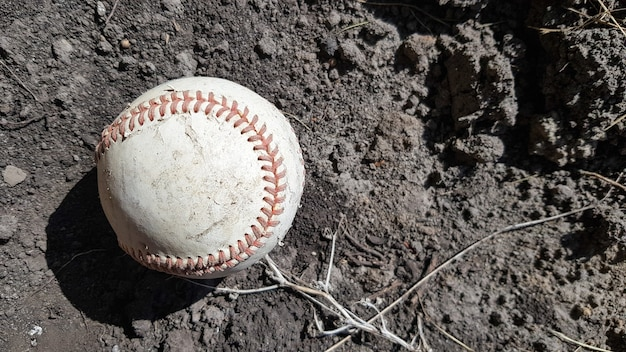 Closeup white leather textured baseball ball with red seams. ball outside stadium home run concept.