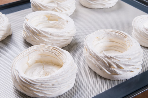Closeup of white meringue nests on tray