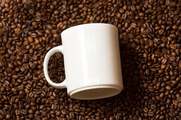 Closeup of white mug lying on roasted coffee beans