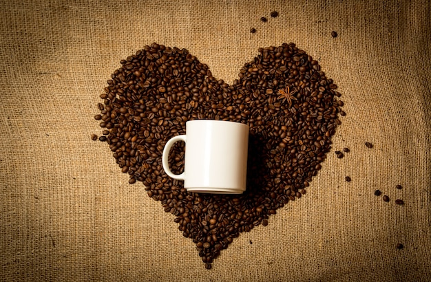 Closeup of white mug in middle of heart made of coffee beans