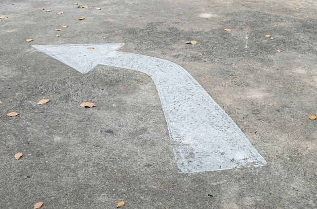 Closeup white painted arrow sign on cement street floor background